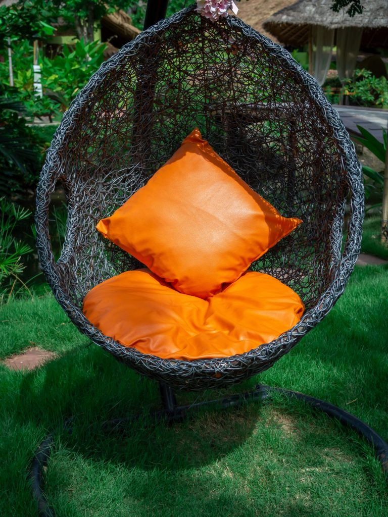 laurel-hill-gardens-rattan-lounger-hanging-egg-chair-with-orange-pillow.